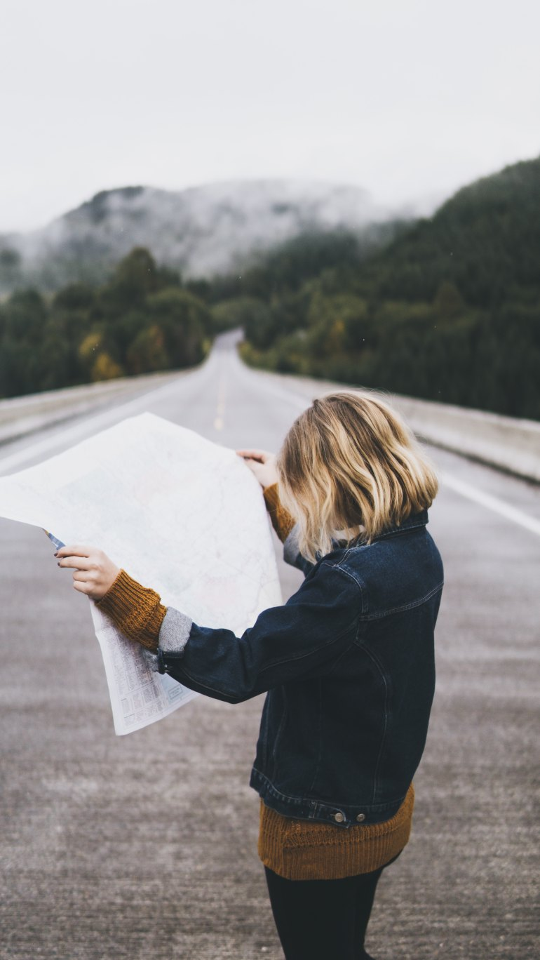 woman reading a map standing in the road