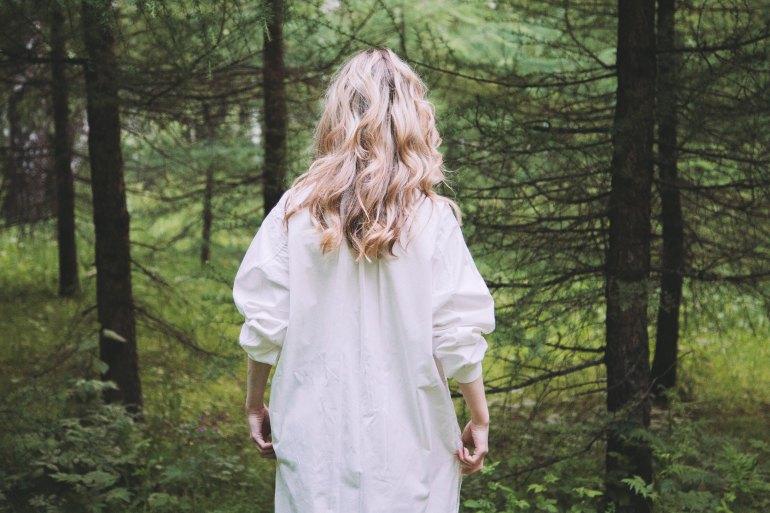girl facing towards the woods