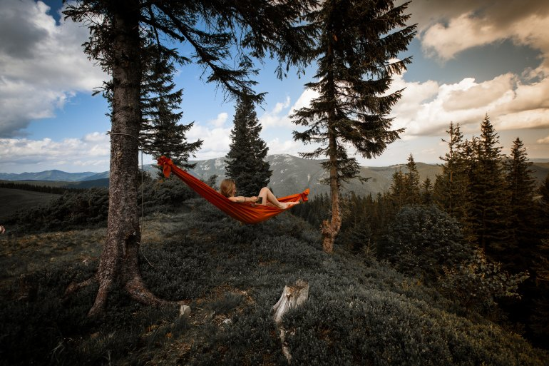 camping woman in American wilderness relaxing hammock between two trees