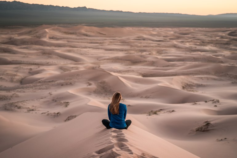 Woman sits facing the distance in Sahara desert