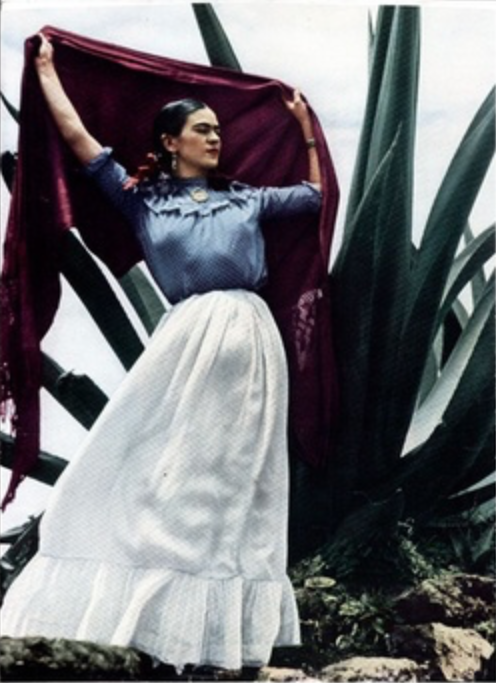 Frida Kahlo holding up her shawl to catch the wind posing with large Mexican plant