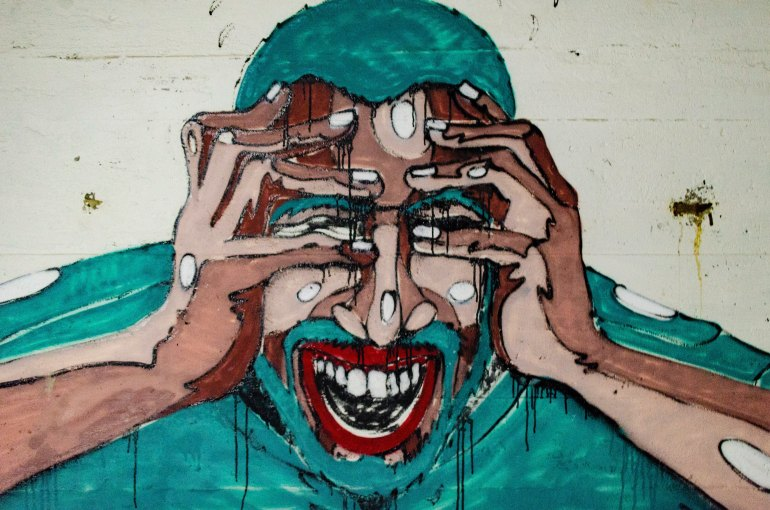 blue red and pink graffiti of a screaming man