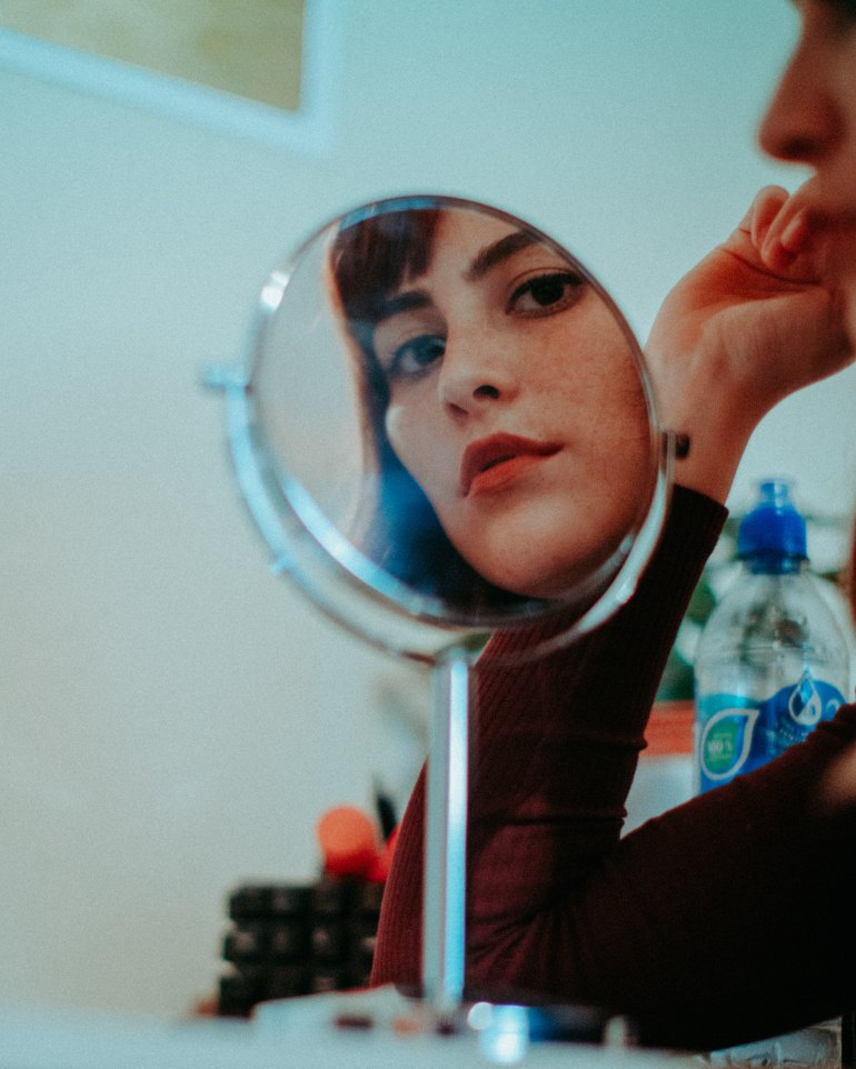 model looks through mirror into the camera