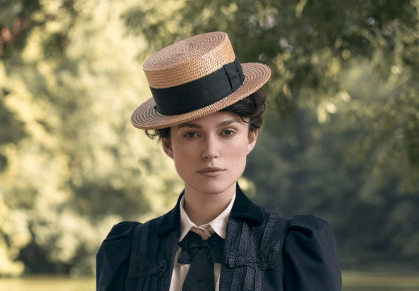 Keira Knightley as Colette standing in park looking into the camera wearing straw boater hat