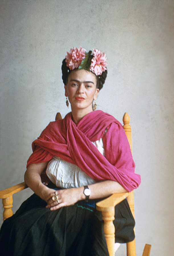 Frida Kahlo seated in photograph with pink flowers in her hair and a bright pink shawl