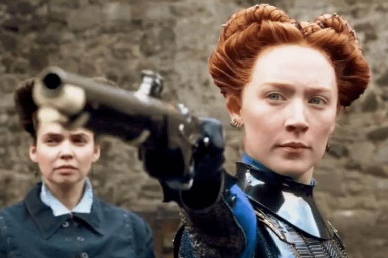 close up of Saoise Ronan as Mary Queen of Scots shooting a gun