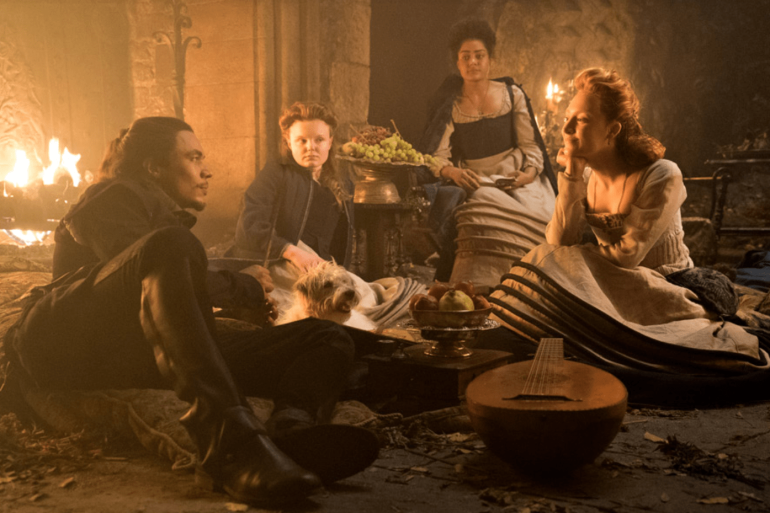 Ronan as Mary Queen of Scots socialising with David Rizzio and ladies in waiting with her dog in front of an open fire