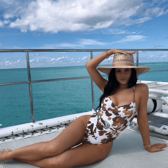 Kylie Jenner wearing a swimsuit and sun hat posing on a yacht in a blue ocean