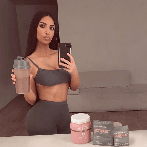 Kim Kardashian wearing activewear posing in a mirror selfie with protein shakes