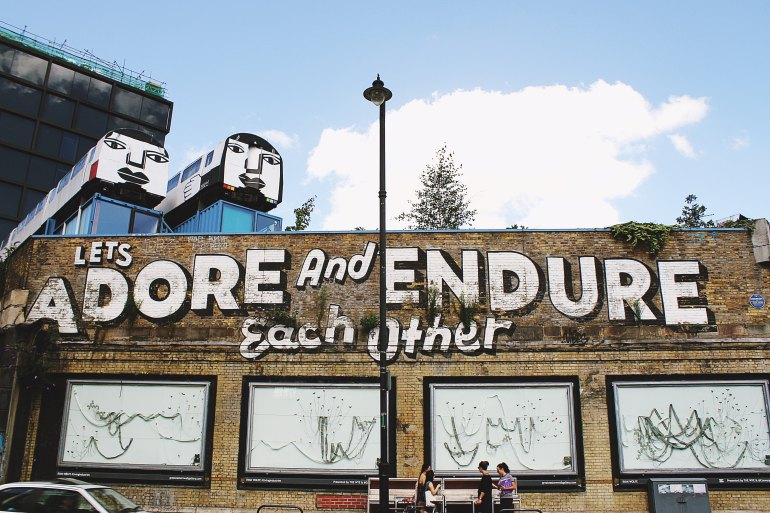 "street art in Shoreditch, London that reads ""let's adore and ensure each other"""